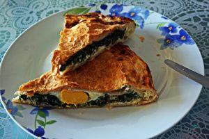 la torta pasqualina genovese: due fette con l'uovo sodo all'interno.